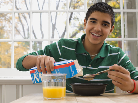 Portrait Of A Teenage Boy Pouring Milk Into A Bowl