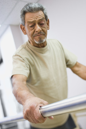 Low Angle View Of A Physically Challenged Senior Man Walking On A Treadmill