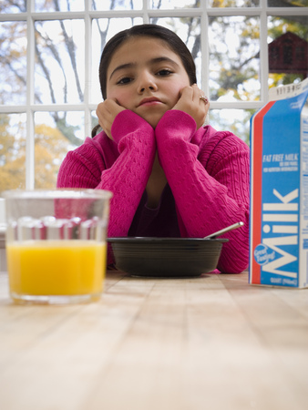Portrait Of A Young Girl Sitting At A Breakfast Table LANG_EVOIMAGES