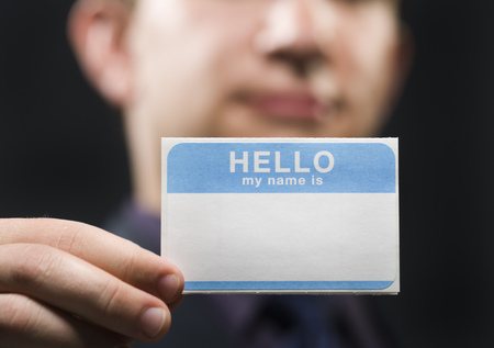 Close-Up Of A Businessman Holding A Name Tag