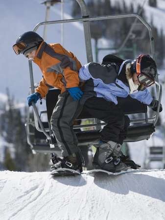 kids at the ski lift: Profile Of A Boy And His Sister Snowboarding Near A Ski Lift