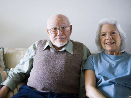 living room sofa: Portrait Of A Senior Couple Sitting On A Couch And Smiling