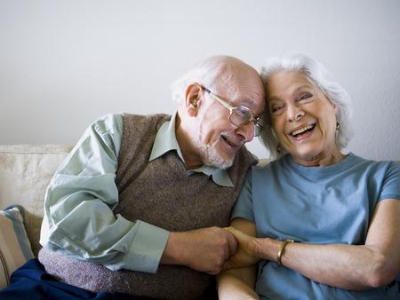 living room sofa: Close-Up Of A Senior Couple Holding Hands