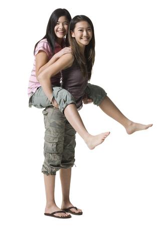 socializando: Portrait Of A Teenage Girl Riding Piggyback On Her Sister