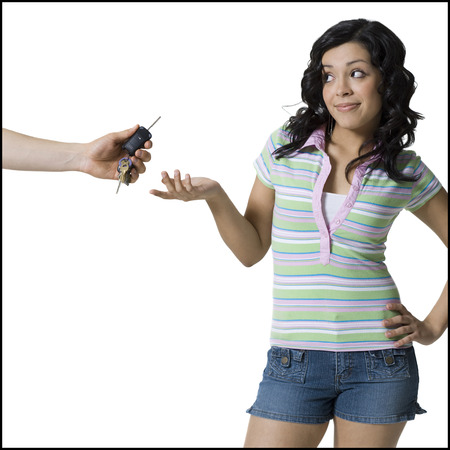 Close-Up Of A PersonS Hand Offering Car Keys To A Teenage Girl LANG_EVOIMAGES