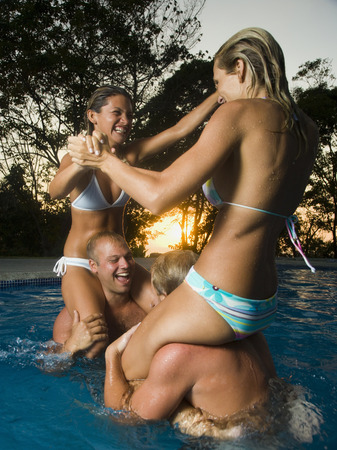 Two Couples Horsing Around In A Swimming Pool