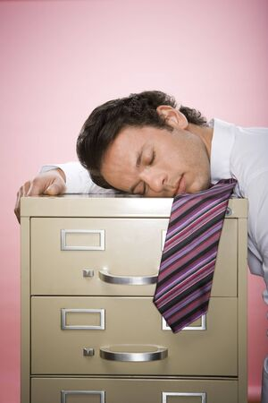 burned out: Close-Up Of A Businessman Resting His Head On A Filing Cabnit