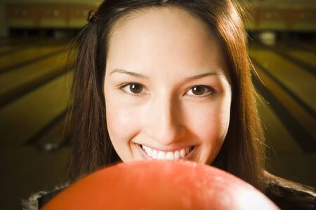 Portrait Of A Teenage Girl Holding A Bowling Ball And Smiling