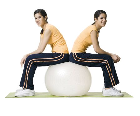Profile Of Two Twin Teenage Girls Sitting On A Fitness Ball LANG_EVOIMAGES