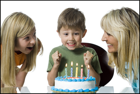kids birthday party: Close-Up Of A Mother And Her Two Children In Front Of A Birthday Cake