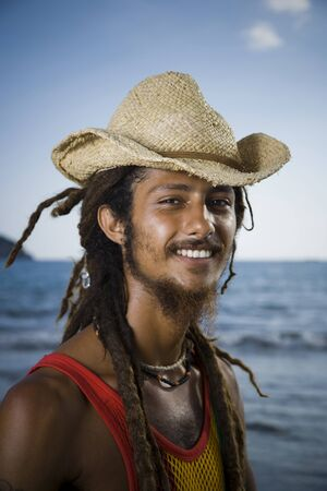 rasta hat: Close-Up Of A Young Man Wearing A Straw Hat