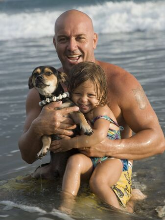 Portrait Of A Man Holding His Daughter And A Puppy In The Ocean