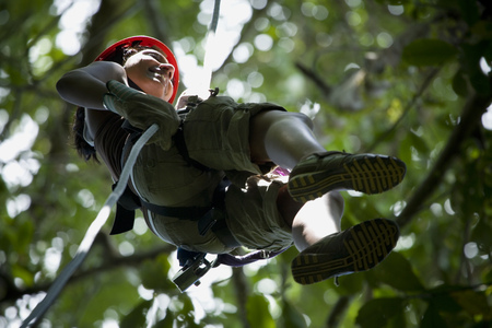 Low Angle View Of A Young Woman Rappelling In The Jungle LANG_EVOIMAGES