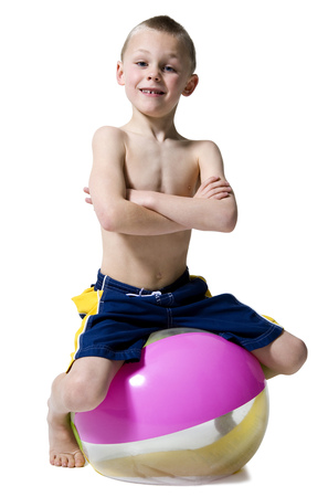 Portrait Of A Boy Sitting On A Beach Ball With His Arms Crossed