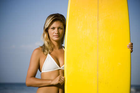 Portrait Of A Young Woman Holding A Surfboard