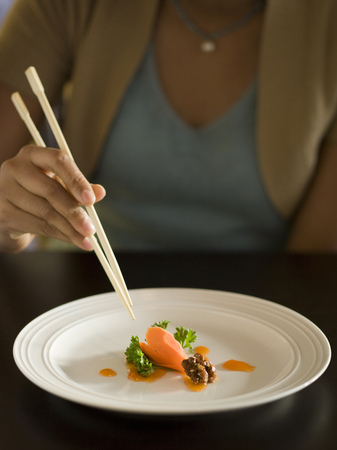 Mid Section View Of A Woman Eating Food With A Pair Of Chopsticks