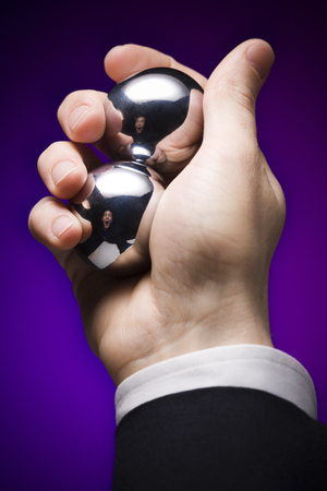 Close-Up Of A BusinessmanS Hand Holding Two Metal Balls