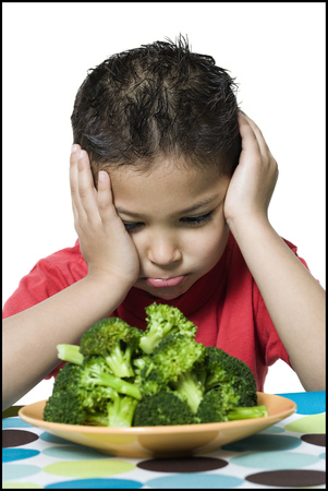Close-Up Of A Boy Looking At Broccoli In A Plate LANG_EVOIMAGES