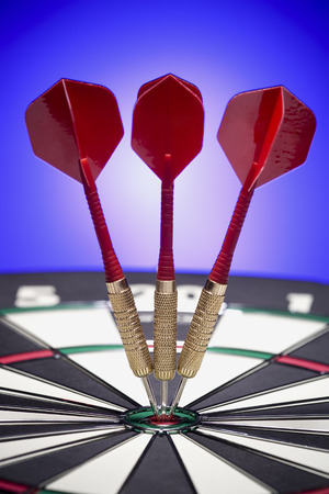 Close-Up Of Three Darts On The BullS Eye Of A Dartboard