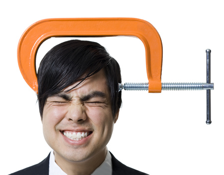 Close-Up Of A Businessman With A Clamp On His Head