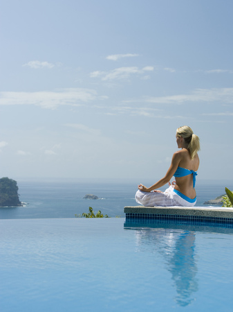 Rear View Of A Mid Adult Woman Sitting In A Lotus Position At The Poolside