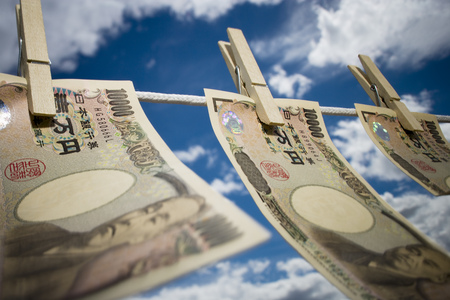Close-Up Of Japanese Currency Pegged To A Clothesline