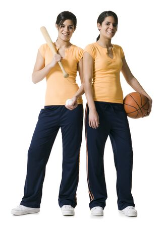 Portrait Of Two Teenage Girls Holding A Baseball Bat And A Basketball LANG_EVOIMAGES