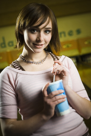 Portrait Of A Teenage Girl Holding A Disposable Glass Of Cola And Smiling LANG_EVOIMAGES