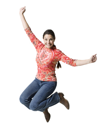 Portrait Of A Woman Jumping In Mid Air With Her Arms Outstretched
