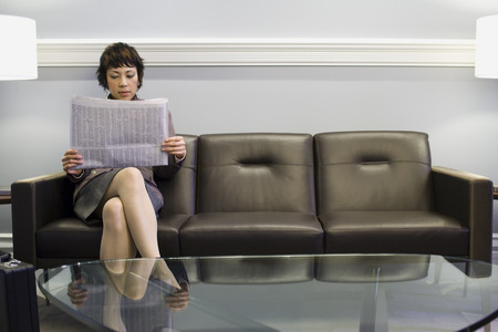 lamp shade: Businesswoman Sitting On A Couch And Reading A Newspaper