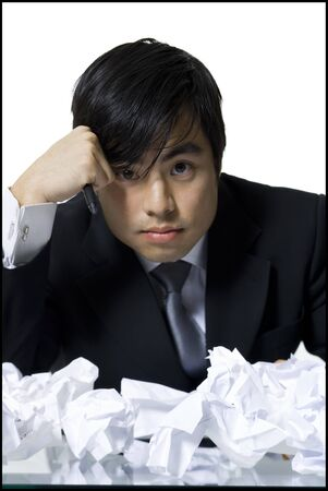 Portrait Of A Businessman Sitting At A Desk Covered With Crumpled Paper