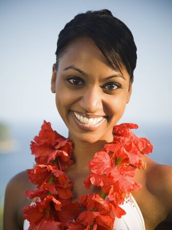 Portrait Of A Young Woman Wearing A Garland Of Hibiscus And Smiling