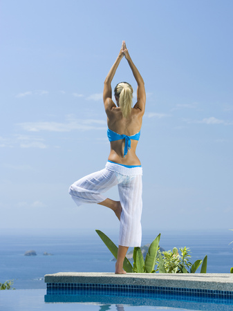 Mid Adult Woman Standing In A Tree Pose At The Poolside