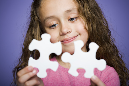 figuring: Close-Up Of A Girl Holding A Puzzle Piece