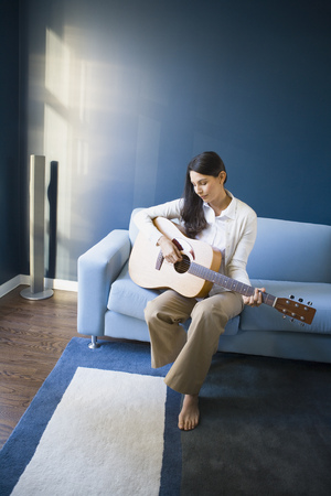 living room sofa: Mid Adult Woman Playing The Guitar