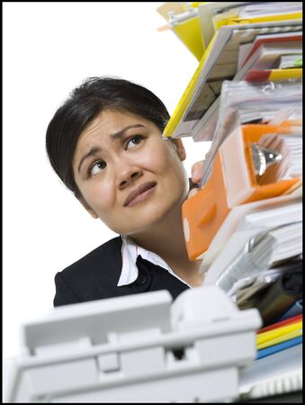 Low Angle View Of A Businesswoman Looking At A Stack Of Files LANG_EVOIMAGES
