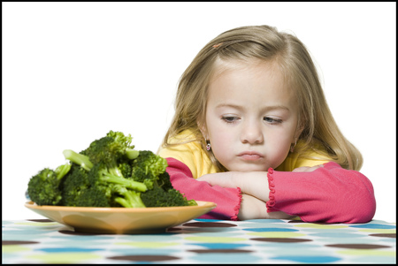 Close-Up Of A Girl Looking At Broccoli