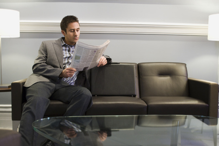 lamp shade: Businessman Sitting On A Couch And Reading A Newspaper