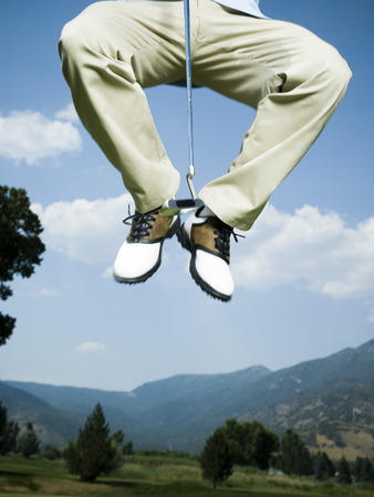 Low Section View Of A Man Jumping In Air With A Golf Club LANG_EVOIMAGES