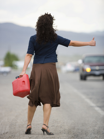 gas can: Rear View Of A Young Woman Holding A Gas Can And Hitchhiking LANG_EVOIMAGES
