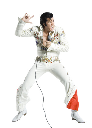 An Elvis Impersonator Singing Into A Microphone And Jumping