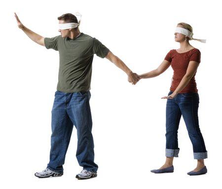 Joven con los ojos vendados llevando a una mujer joven con los ojos vendados LANG_EVOIMAGES