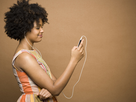 Profile Of A Young Woman Listening To An Mp3 Player LANG_EVOIMAGES