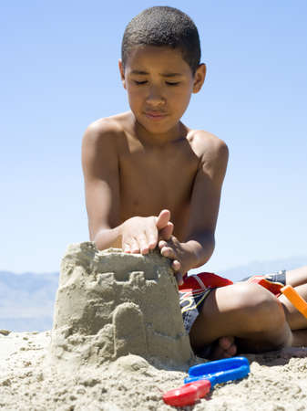 Close-Up Of A Boy Making A Sand Castle