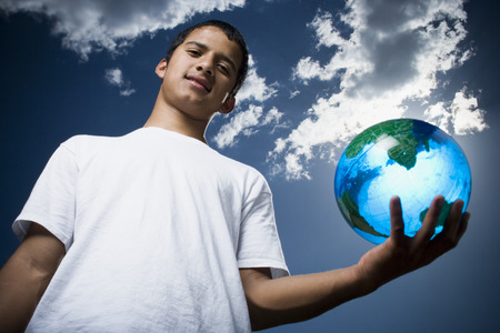 Portrait Of A Teenage Boy Holding A Globe
