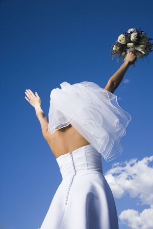 Low Angle View Of A Bride Holding A Bouquet Of Flowers With Her Arms Raised