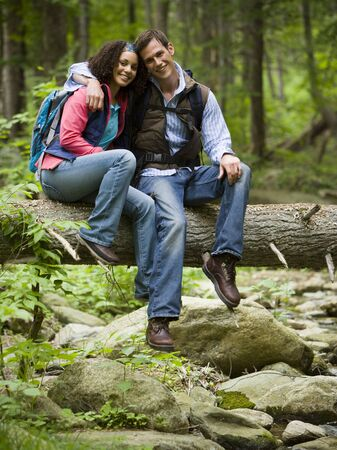 Portrait Of A Young Couple Sitting On A Fallen Tree