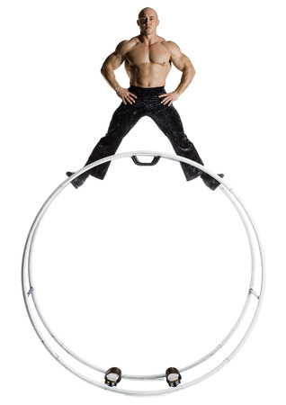 Male Bodybuilder Posing On Top Of German Wheel