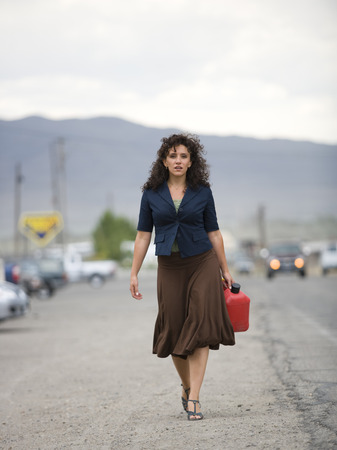 gas can: A Young Woman Walking With A Gas Can LANG_EVOIMAGES