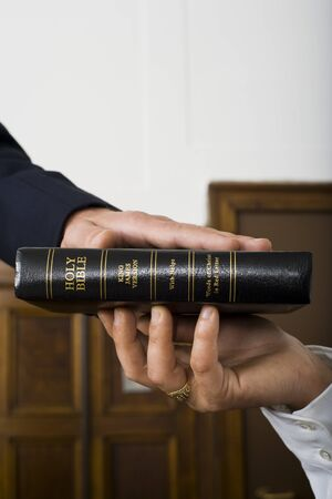 Close-Up Of A Witnesses Hand Swearing Over The Bible